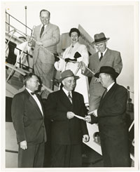 Black-and-white photographic print, 8 x 10 inches. Norgaard is standing on gangplank of the vessel. He is on the left. There is one woman and a man next to him on the stairs. Three men are standing below on the dock. The men are all wearing suits, some wearing hats. The Mokuhana name is seen painted on the vessel in the background.