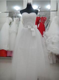 Vestido de novia corte princesa, sin mangas, con apliques de pedrería en el pecho y cinturón con lazo