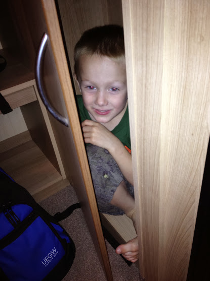 boy hiding in cupboard