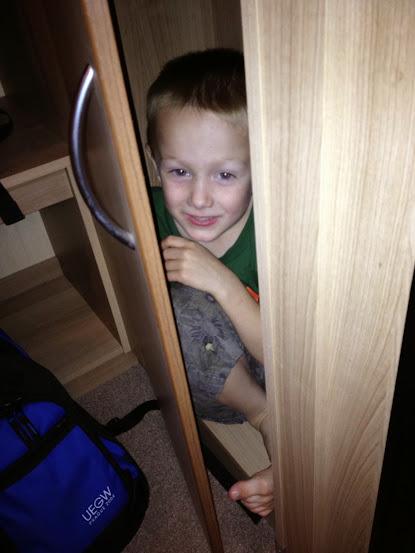 boy hiding in cupboard