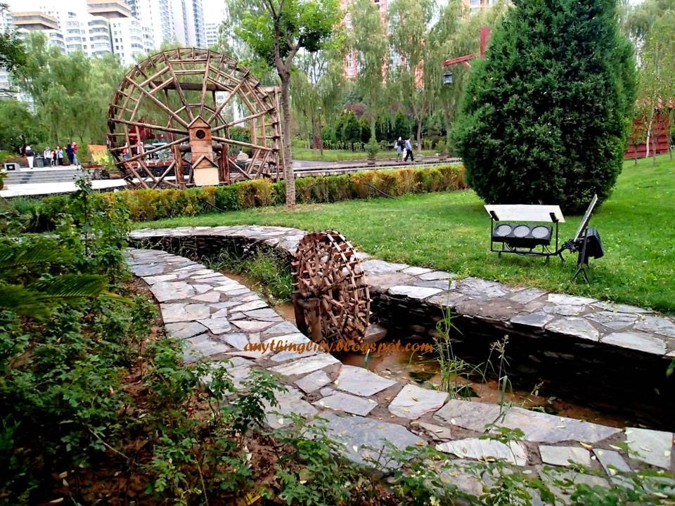 Waterwheels Of Varying Sizes Certainly Add Charm To This Park. (pic Shows A  Waterwheel Of Miniature Size).