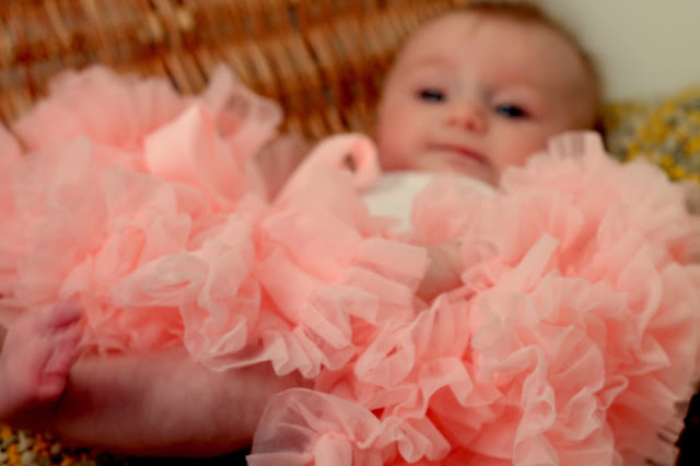 baby led in basket in pink tutu with yellow and grey blanket