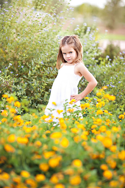 Little girl poses for Tucson Photographer with flowers in the foreground