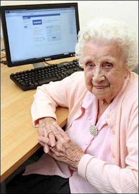 An old lady sitting in front of a computer with facebook on the screen