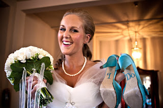 Nicole holding her blue wedding shoes and bouquet