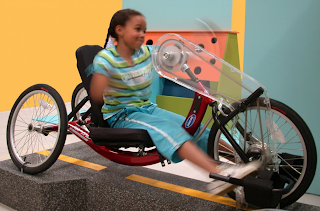 image of girl with physical disability riding an adapted bike.