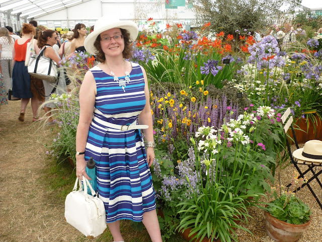 Side view of Striped blue and white dress against floral display