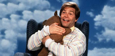 Al Franken, in his role Stuart Smalley, hugging a teddy bear