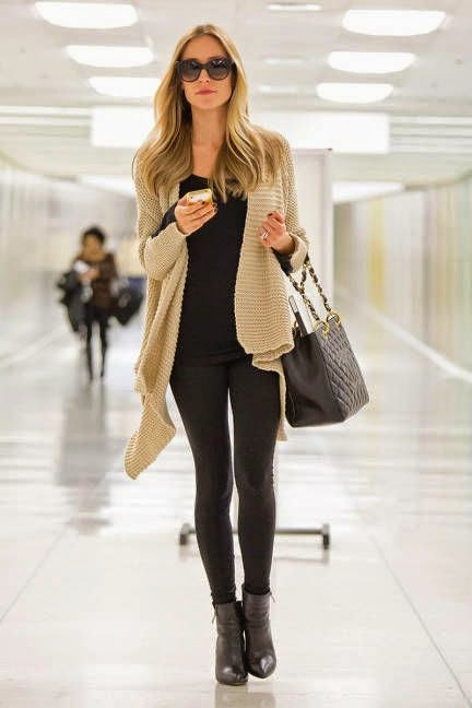 Layer a neutral, chunky knit over black leggings for a sophisticated travel look—and a Chanel purse never hurts.