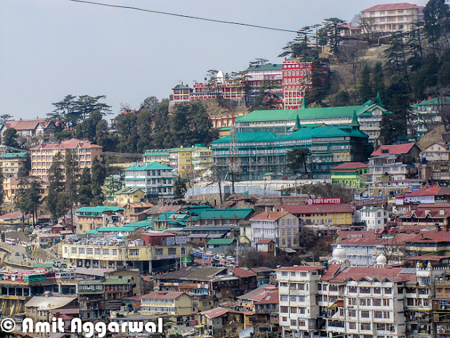 After some wonderful Photo Journeys from Shimla (IIAS, Jakhu & Sankat Mochan), here is another one by Amit Aggarwal. This Photo Journey shares more about Shimla Town and it's beauty.First photograph of this Photo Journy shows a very old Clock on Mall Road. This is places at BSNL office building, which is just in the beginning of Mall Road when we come from Himachal Pradesh University at Summer Hill.Here is a colorful building on other end of Mall Road of Shimla. Although Hotel hoardings are on left side of the building, but it's office of various High Court Advocates.Here is a main Gate of High Court Shimla. High Court Shimla is near to Mall Road and parking area is just next to mall road only.Most of the buildings around Shimla are quite interesting with slanting roofs, which are important in regions which get heavy snowfall and rains.Shimla is extremely dense and day by day it's spreading like other big cities of India. During a short visit to Shimla, every tourist like this city - It's beauty, freshness and weather. But Shimla has nt enough resources for people living there. Water is one of the biggest problem during summers. This sounds weird that hill station faces water-problem in summers, but that's true. Shimla has not big river nearby and the way population is increasing, it's always difficult to meet the requirement even when every year lot of efforts go into bringing water to the town from surrounding riversSince town was not planned to handle this much population, not we can easily see severe traffic jams around roads in Capital City of Himachal. Parking is one of the biggest problem as majority of families have four wheelers now and hardly any space to park. Tourism department has tried to solve parking problem for tourists who visit the town in their own carsColorfulness of houses in Shimla is very attractive and different from other cities. Being a hilly station, it has a big opportunity to do show-off because more number of houses can be seen at one point of time, which is not that possible in plains Here is a photograph of starting of shopping area on Mall Road, which is quite near to office of District Commissioner and Kalibari Temple. The building on left  is BSNL head office of Himachal Pradesh and on right are various showrooms having brands like Reebok, Adidas. There is a shop called 'City Point' near the beginning which is very famous for pastries..Mall road is most popular place in Shimla for Shopping. Apart from popular brands, there are some interesting shops to get woolens, stuff for kids and girls etc.Many offices of Shimla are around Mall Road and others are towards Chhota Shimla and New Shimla region. Here is a photograph showing SP office of Shimla. Most of the office buildings are old and built in British styleShimla Townhall, which is quite popular among Bollywood folks. Most of the bollywood folks who come to Shimla for shooting, choose this building of one or more shots. Movies like Kareeb are almost completely show around this place. This is center of Mall Road and most crowded place around Ridge ground of Shimla A view of beautiful Church on Ridge, Shimla. This photograph is clicked from Mall Road which is just below this Church.A view of World's highest Hanuman Statue at such a high altitude. This photograph is shot from Mall Road and this statue  is higher that these high deodar trees. It's 108 feet high ! To know more about Jakhu Temple and this Hanuman Statue, please check out - http://phototravelings.blogspot.com/2012/04/jakhu-temple-with-worlds-highest.htmlHere is a photograph of Indira Gandhi State Sport Complex which is located in the middle of Mall Road, which is just in front of HPTDC Lift. Indira Gandhi Sports Complex in Shimla is a very famous complex not only in Himachal Pradesh but also in India. It provides all required facilities for organizing events of sports as well as trade. This complex has been organizing so many events for a longer period of time. The venue is liked by sports and other event organizers as they get enjoyments together, one they do their professional work and two they get a chance to see the natural sight of Shimla. IGSS complex provides a very big space which can be utilized as per the requirement of an indoor as well as outdoor event. The complex provides good facility to sit and to enjoy for the people who get there to entertain them.