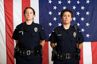 Female officers stands in front of an American flag.