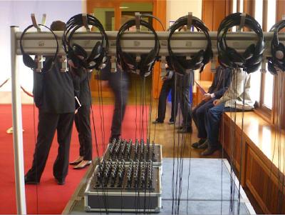 Menschen warten auf die Pressekonferenz; durch die Kopfhörer hindurch und über den Tisch mit Empfangsgeräten hinhinweg betrachtet