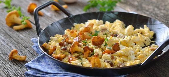 poza omleta cu ciuperci chenterelle : o tigaie plina cu mancarea pusa pe masa de lemn pe un prosop ca sa nu se arda, inconjurata de cateva ciupercute si verdeata pentru un aspect placut.