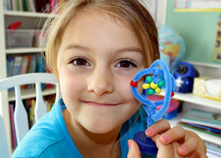 """Using Janice VanCleave's """"83. Building Blocks"""" experiment as a guide, Tessa created a model of a lithium atom with a plastic milk jug cap, pipe cleaners and colored pony beads."""
