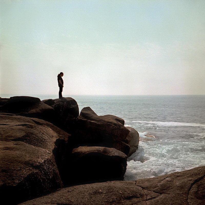 Lavadores junto ao mar, lugar com costa rochosa e mar muito agitado. Na foto um homem sobre as rochas do primeiro plano, a observar a paisagem, contra um fundo de céu claro com uma leve névoa