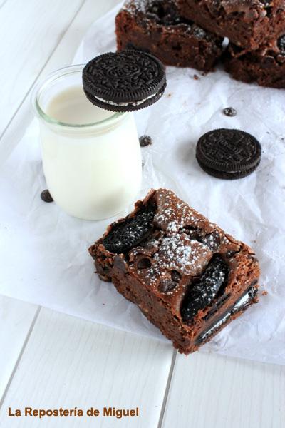Foto aérea de porción de brownie con jarrita de leche transparente y en el borde de la jarrita una galleta, encima del papel hay galletas oreo y pepitas de chocolate.Todo ello sobre una mesa de madera blanca.