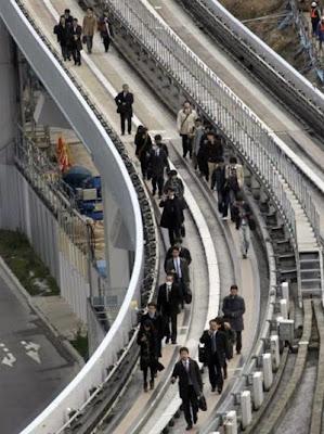 Pasajeros del tren Yurikamome andando en un paso elevado hacia la estación Shiodome de Tokio (de El País)