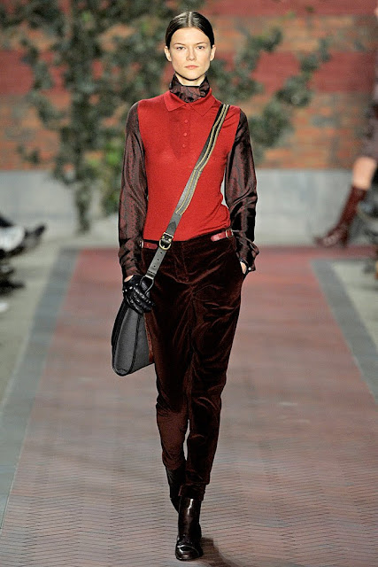 model from tommy hilfiger's fall 2012 runway show wearing rust velvet pants,a red vest with a peter pan collar and shiny brown long sleeve shirt holding an across the body bag