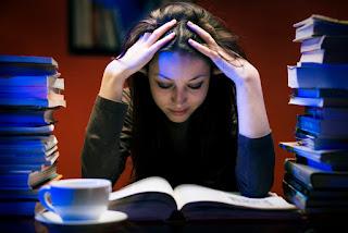 chica tomandose la cabeza mientras estudia
