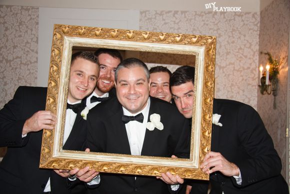 These groomsmen pose with a fun gold frame on the wedding day.