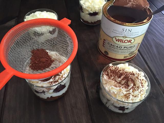 Tiramisú de cerezas. Espolvoreando con el cacao en polvo Valor.