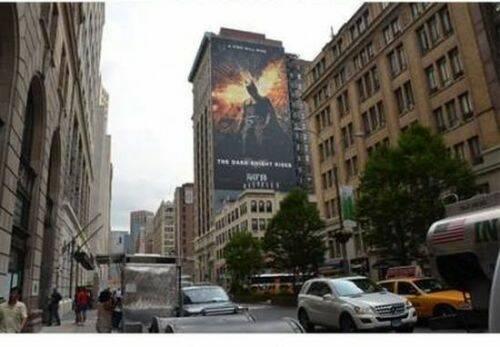 Arte: un Hombre pintando un poster de Batman en un Edificio