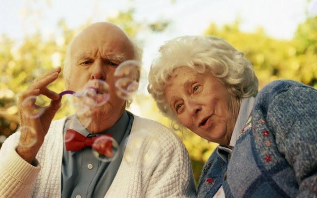 пожилая пара веселится и пускают мыльные пузыри