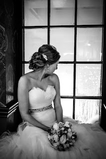 Bride in gown adorned with feathers gazing out the window while being photographed