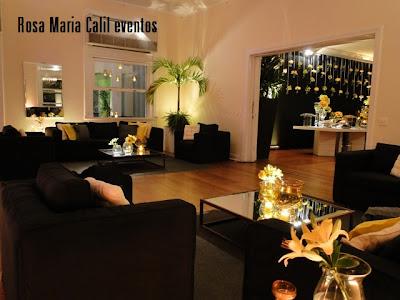 sofá preto, mesa centro espelhada, almofadas amarelas e brancas, velas, decoração, 15 anos