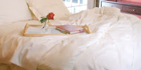 A bed with white sheets, a white puffy quilt, white pillows, and a tray with a red rose in a small vase and a book or journal.