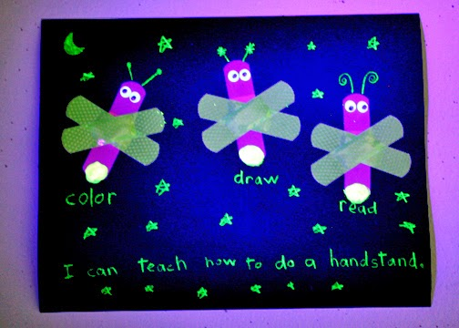 "Tessa's completed ""Bandage Lightning Bugs"" craftivity as it appears under a black light in a darkened room."