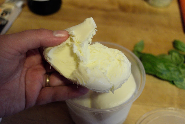A ball of fresh mozzarella being torn apart.