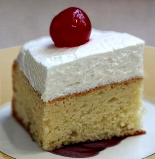 Tres Leches Cake with sweet cream frosting and cherry on top. The cake stays moist by soaking in sweet milk. Can be served with any fruit topping. Plain is delicious, too. Homemade recipe is easy to follow.