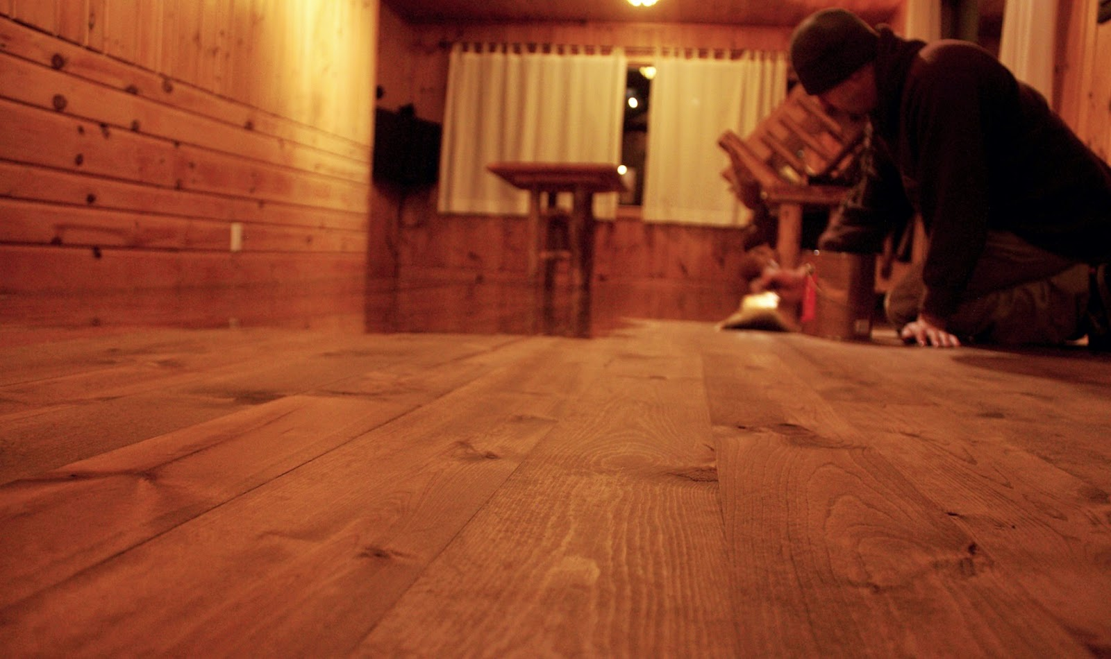 Chris Kuehn putting the first coat of finish onto the newly laid floor.