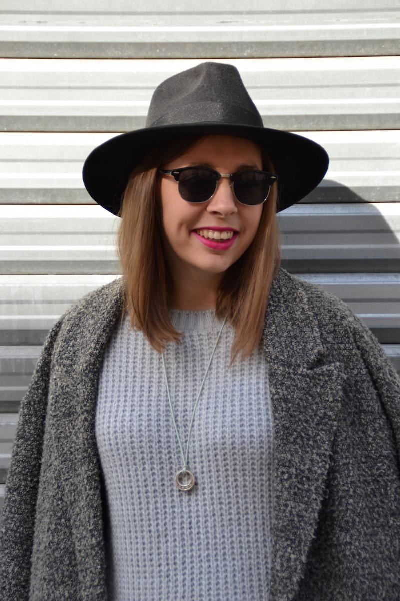 manteau gris oversize H&M, robe pull grise Boohoo et chapeau noir New Look et collant à pois Calzedonia, sac Balenciaga