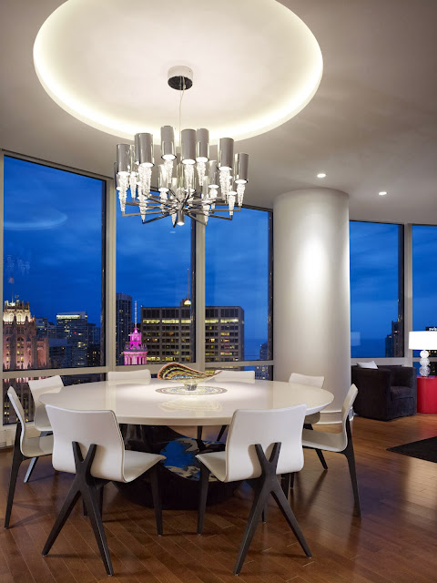 outstanding round dining with hovering contemporary lighting above and city view by the glass walls