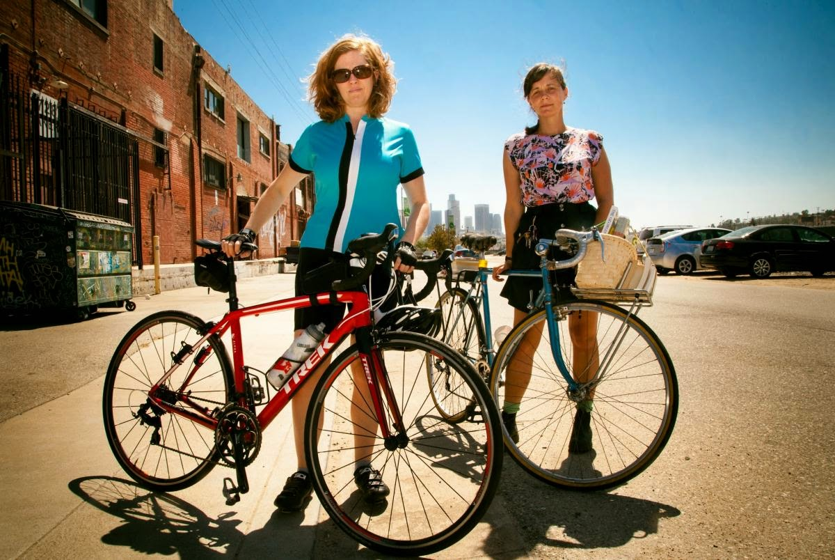 Two women stand holding their bicycles on a city street
