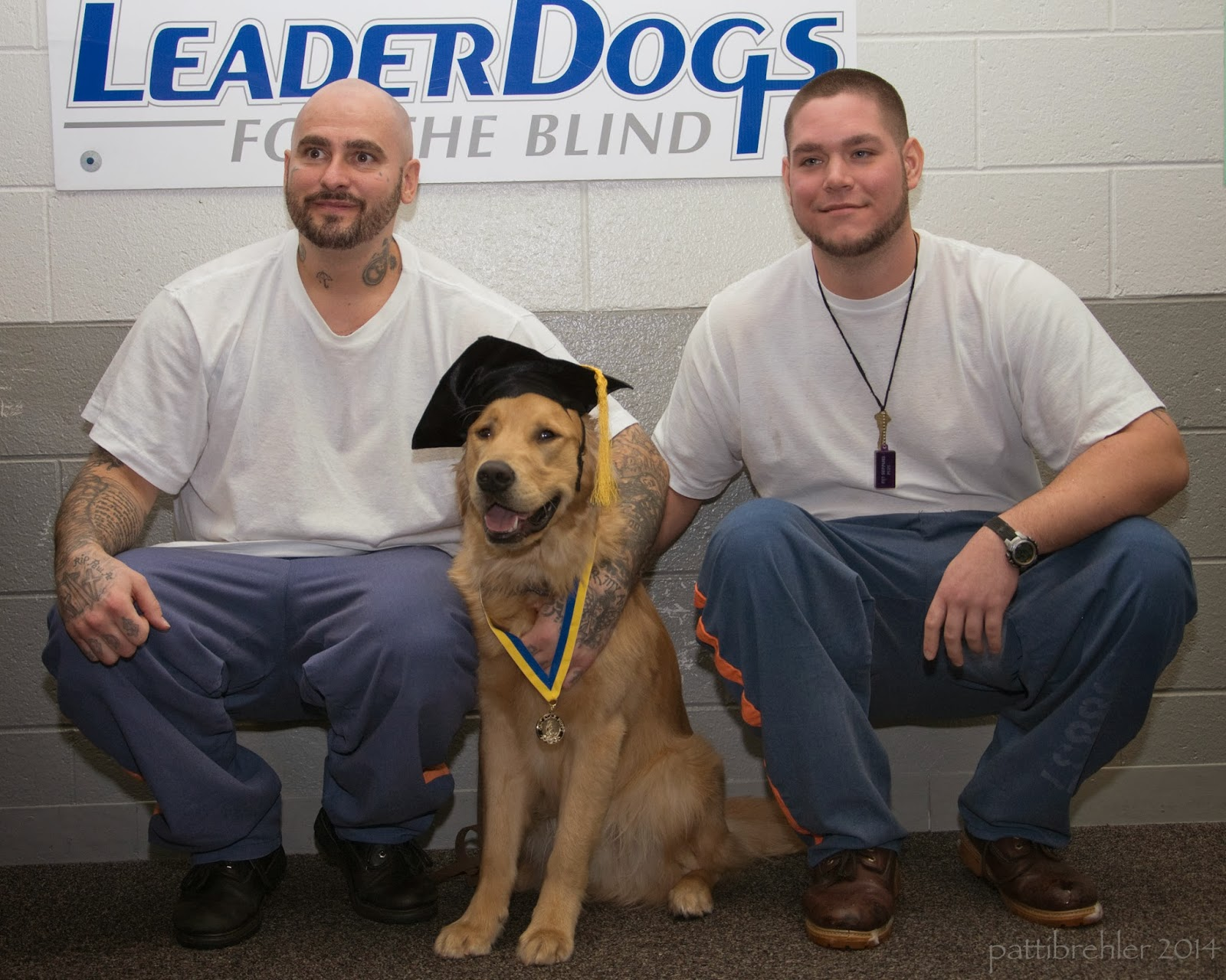 Two men are squatting down with a golden retriever sitting betweent hem. The men are wearing white t-shirts and blue pants. The golden retriever is wearing a black graduation cap and a yellow and blue ribbon with a medal around its neck. Behind them on the wall is a white poster with Leader Dogs for the Blind on it.