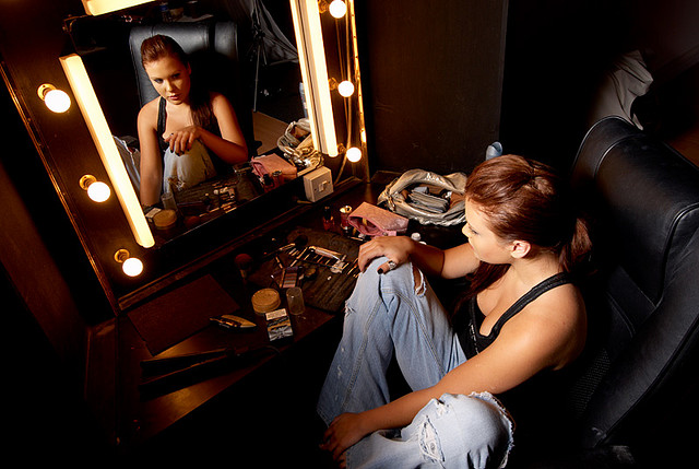 A makeup artist sitting in a dressing room