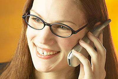 woman smiling and speaking on telephone