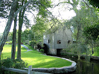 Gray grist mill with pond and trees.