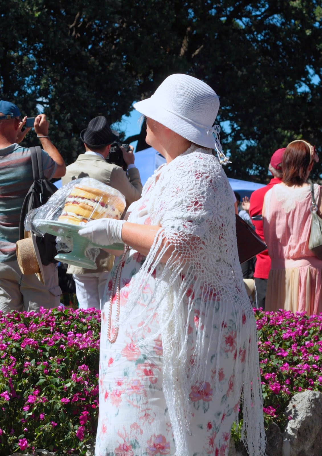 Woman in a cloche hat and crocheted shawl carries an enormous cake.