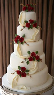 5 tier white wedding cake with red roses
