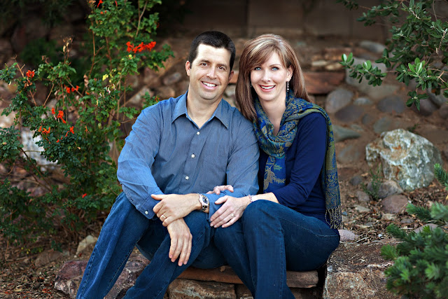Posed photograph of a Tucson husband and wife with their garden in the background
