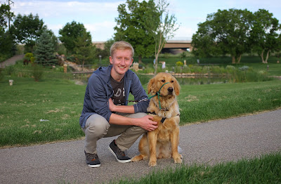 Ian smiles posing with a Golden Retriever guide dog puppy with a green field and trees behind them.