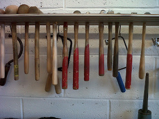 A row of tools hanging from a woodent shelf