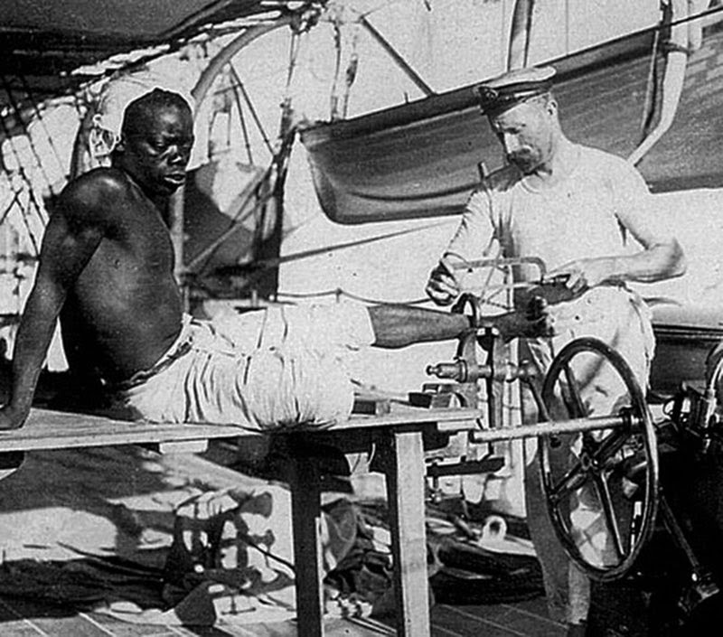 A British blacksmith removing the leg irons off a slave, 1907