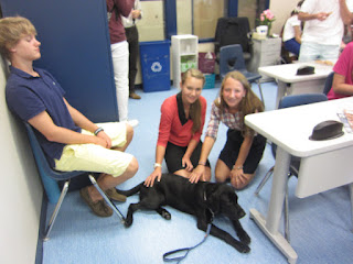 Two girls from Coach Daly's advisory are petting Coach.