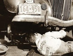 Vintage photo of mechanic working on car with DC plates
