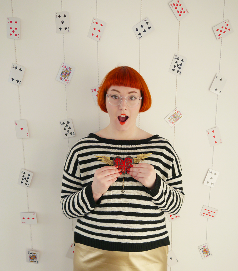 Queen of Hearts, Alice in Wonderland, Queen of Hearts outfit, red queen, literary style, Karen Smith jewellery, heart jewellery, Dundee jewellery, Dundee design, Scottish jewellery design, red  hair, dinger, Scottish blogger, pack of cards, Iolla glasses, clear glasses, red lips, doll lips, stripey jumper, gold skirt, red glitter hearts, mechanical heart brooch, moveable jewellery, interactive jewellery, winged heart brooch
